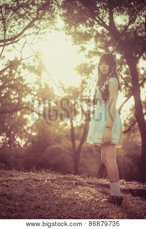 Cute Asian Thai Girl Is Standing In The Evening Sunset Through The Wilderness In Vintage Color