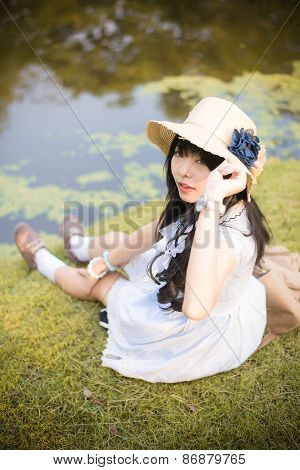 A Cute Asian Thai Girl Is Relaxing Near The Pond In The Wilderness