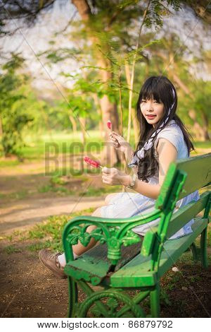 A Cute Asian Thai Girl Is Sitting On The Bench Holding An Ice Cream