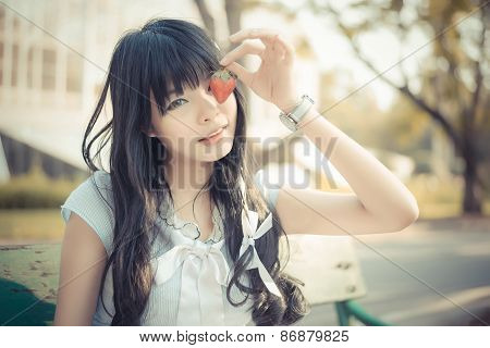 A Cute Asian Thai Girl With Vintage Clothing Is Picking A Strawberry With Cute Facial Expression In
