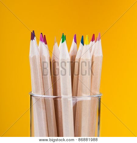 Colorful wooden pencils on yellow background