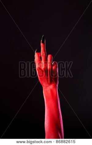 Red devil hand with black nails showing middle finger, studio shot on black background