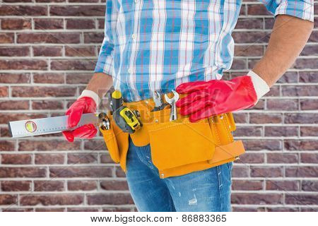 Midsection of handyman holding spirit level against red brick wall