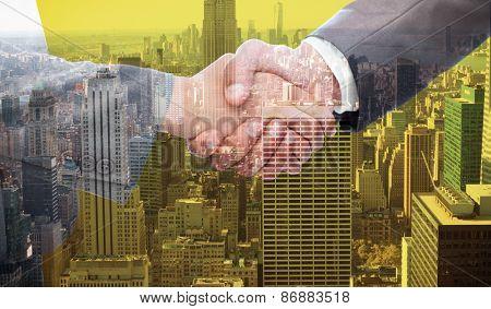 Handshake between two business people against city skyline