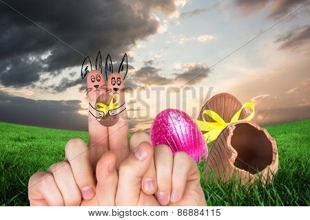 Fingers as easter bunny against broken easter egg