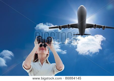 Businesswoman looking through binoculars against sky