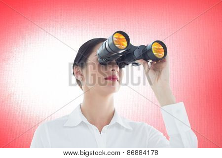 Business woman looking through binoculars against digitally generated grey background