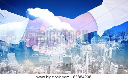 Close-up shot of a handshake in office against high angle view of city