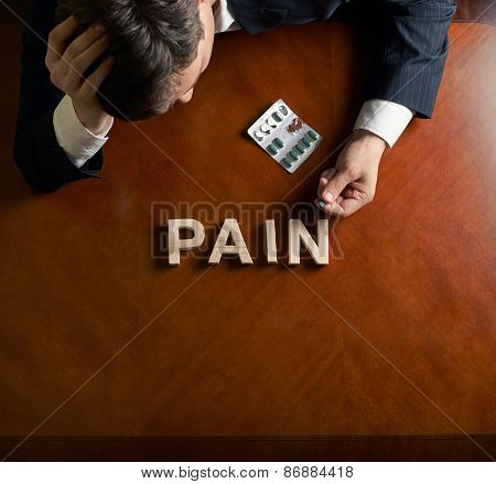 Word Pain and devastated man composition