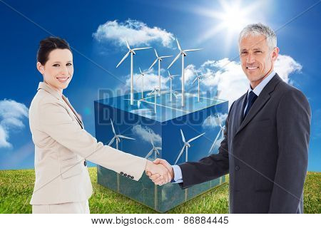 Smiling business people shaking hands while looking at the camera against wind turbines on cube showing more wind turbines