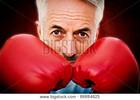 Close-up portrait of a determined senior boxer against dark background