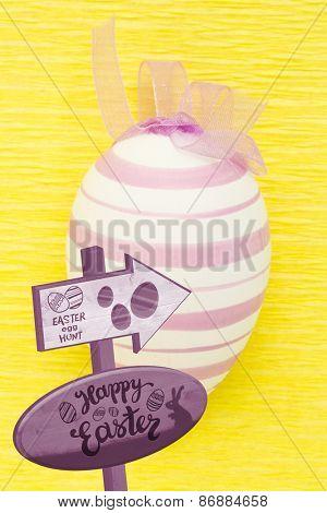 Easter egg hunt sign against close up on purple easter egg