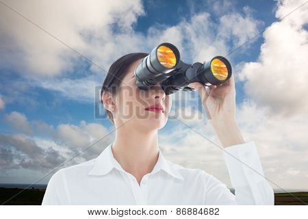 Business woman looking through binoculars against blue sky with white clouds