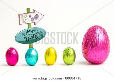 Easter egg hunt sign against four small easter eggs beside large one