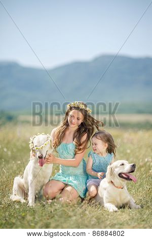 Two sisters are resting and having fun in the flower field in the summer with their dogs.