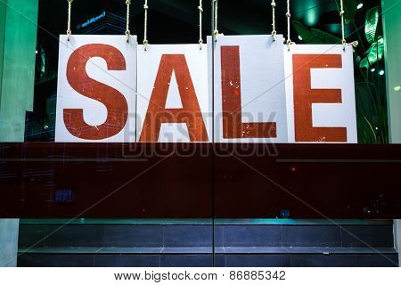 sale poster in fashion shop display window