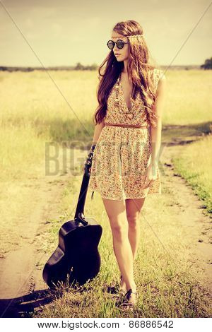 Romantic girl travelling with her guitar. Summer. Hippie style.
