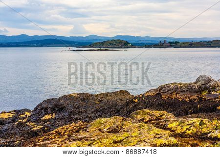 Black Sands beach Aberdour Scotland. Aberdour has two beaches - the Silver Sands and the Black Sands.The Black Sands as the contrasting name would suggest have a rockier and darker sand and are also popular with visitors exploring the rock caves and fasci