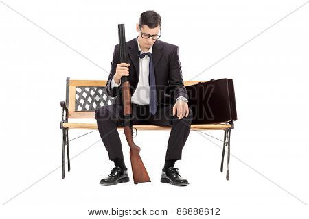 Depressed young businessman holding a shotgun rifle and looking down seated on a wooden bench isolated on white background