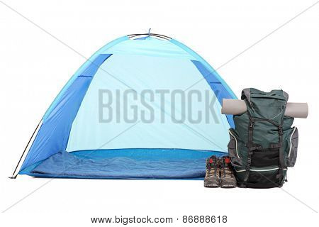 Frontal shot of blue tent, a rucksack with hiking equipment and a pair of boots isolated on white background