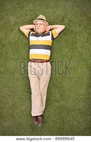 Relaxed senior gentleman lying on grass in a field and looking up in the sky