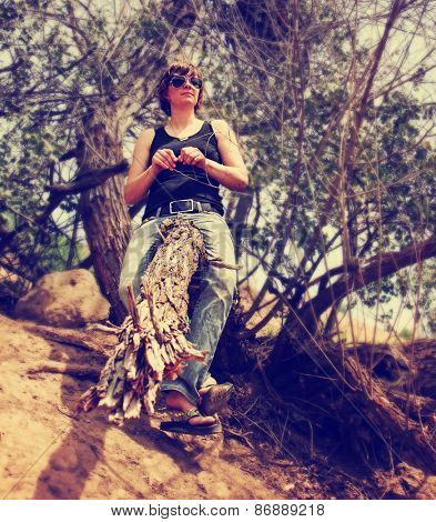 a woman sitting in an old gnarly tree during summer toned with a retro vintage instagram filter effect app or action