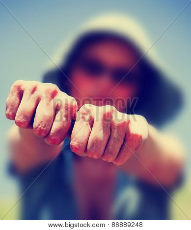a blurred out woman holding her hands in fists toward the camera toned with a retro vintage instagram filter effect app or action