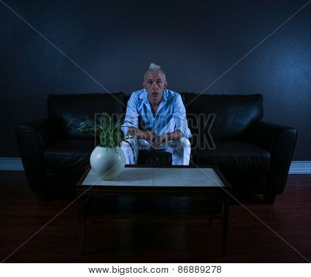 a young man enjoying watching a movie at home sitting on the couch