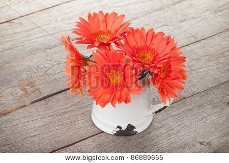 Orange gerbera flowers in pitcher on wooden table