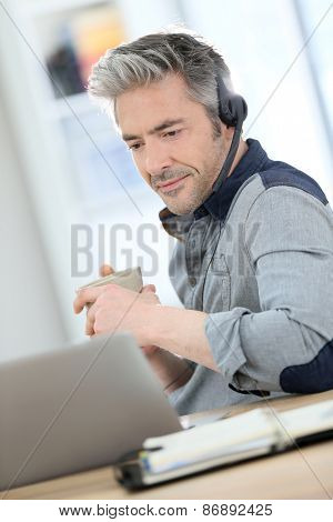 Mature man teleworking from home with laptop