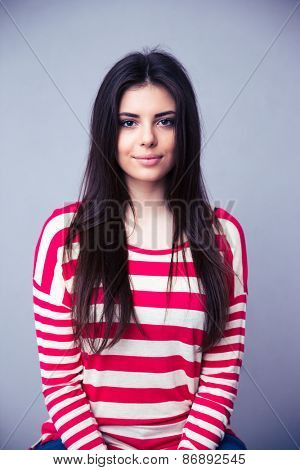 Portrait of a charming young woman over gray background. Looking at camera