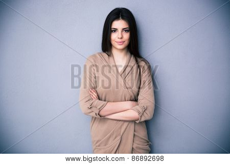 Happy beautiful woman with arms folded standing over gray bakground. Looking at camera