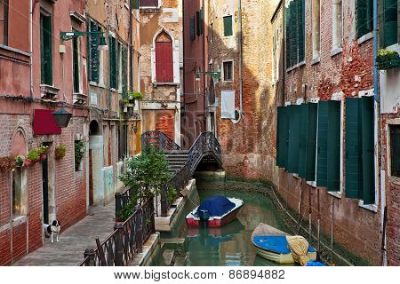 Boats on narrow canal among typical old houses in Venice, Italy.