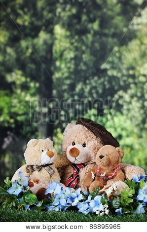 Three toy bears -- a papa, son and daughter bear, cuddled together on a lawn near the woods, with room for your text in the trees above and behind.