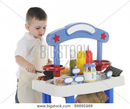 A young preschooler grilling hot dogs on his vendor stand.  The stand's signs are left blank for your text.  On a white background.