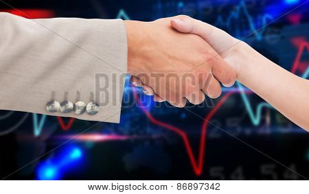 Close up of female and male hand shaking against stocks and shares on black background