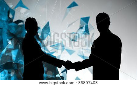 Smiling business people shaking hands while looking at the camera against angular design