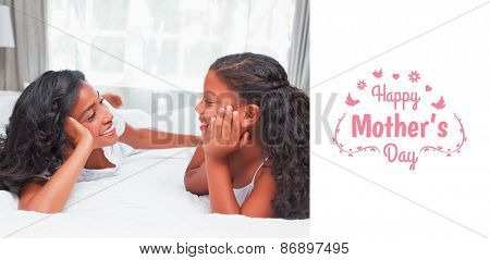 mothers day greeting against smiling mother and daughter posing together on bed