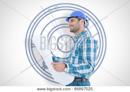 Smiling engineer looking away while holding blueprint against blueprint