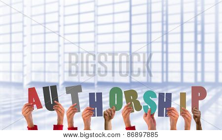 Hands holding up authorship against room with large window overlooking city