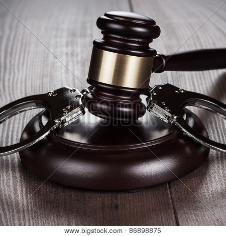 handcuffs and judge gavel on brown table