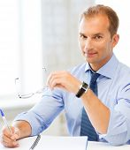 image of spectacles  - picture of handsome businessman with spectacles writing in notebook - JPG