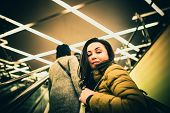 stock photo of escalator  - Long hair girl on the escalator in the shopping center - JPG