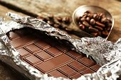 picture of chocolate spoon  - Bar of chocolate in foil with coffee beans in spoon on wooden table - JPG