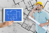 stock photo of blueprints  - Male architect with blueprint talking on mobile phone against digital tablet displaying blueprint - JPG