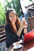 pic of handphone  - A portrait of a Young businesswoman work oudoor in a cafe - JPG