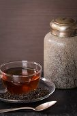 picture of black tea  - Scattered dry tea leaves in glass cup of tea and vintage jar on black background - JPG
