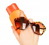 stock photo of suntanning  - Bottle of suntan cream and sunglasses in female hands isolated on white - JPG