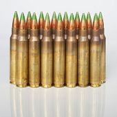 stock photo of cartridge  - Cartridges loaded with bullets that have a green tip on a white background and slight reflection - JPG