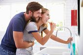 foto of pajamas  - Couple In Pajamas Brushing Teeth In Bathroom - JPG